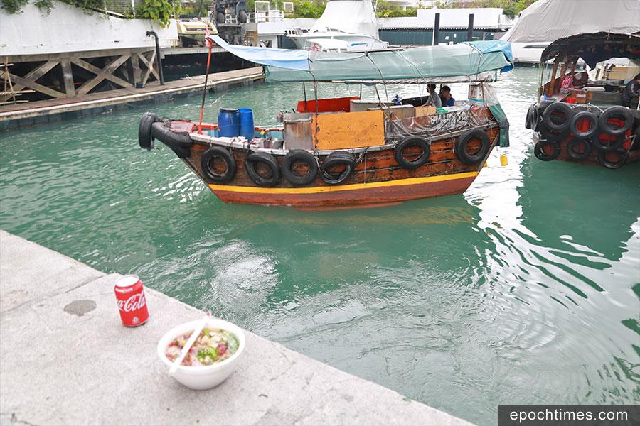 肥仔的艇仔粉亦深受老饕的愛戴,在珍寶海鮮舫一帶有不少捧場客。圖中背景的小艇為肥仔經營的粉艇,前方岸邊為肥仔發售的艇仔粉和飲料。(陳仲明/大紀元)