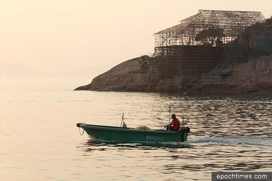 黃昏時分,蒲台島鄉民樹哥乘着小艇出海捕魚。(陳仲明/大紀元)