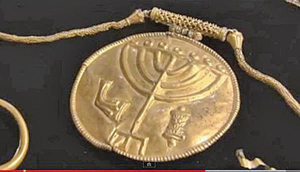 出土的寶藏中有一個直徑十釐米的黃金浮雕獎章,上面刻有象徵猶太人的燭台、羊角號和一個摩西五經經卷(Torah scroll)。(視頻截圖)