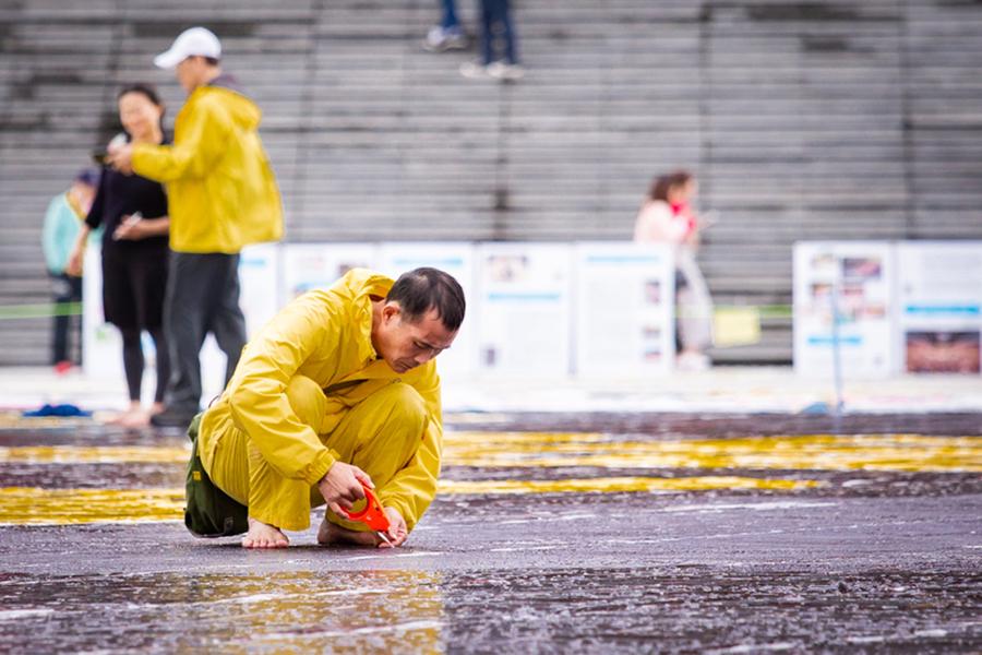 台灣法輪大法學會11月24日在台北中正紀念堂舉行排字活動前,法輪功學員齊心協力,進行排字前的準備工作。(陳柏州/大紀元)