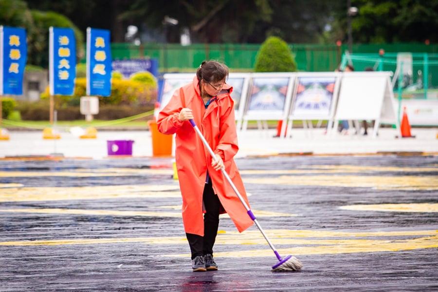 台灣法輪大法學會11月24日在台北中正紀念堂舉行排字活動,法輪功學員進行排字前的準備工作,並清除座墊上的積水。(陳柏州/大紀元)