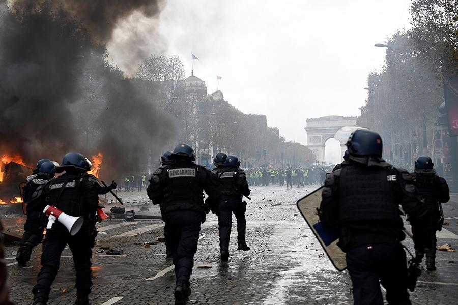 巴黎24日香榭麗捨大街警民對峙。(BERTRAND GUAY/AFP/Getty Images)