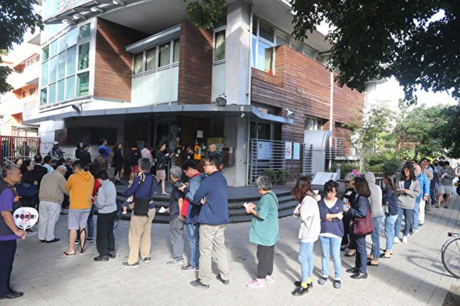 台灣2018年地方公職人員選舉及全國性公民投票案第7案至第16案11月24日登場,天氣晴朗,民眾一早出門排隊投票。(中央社)