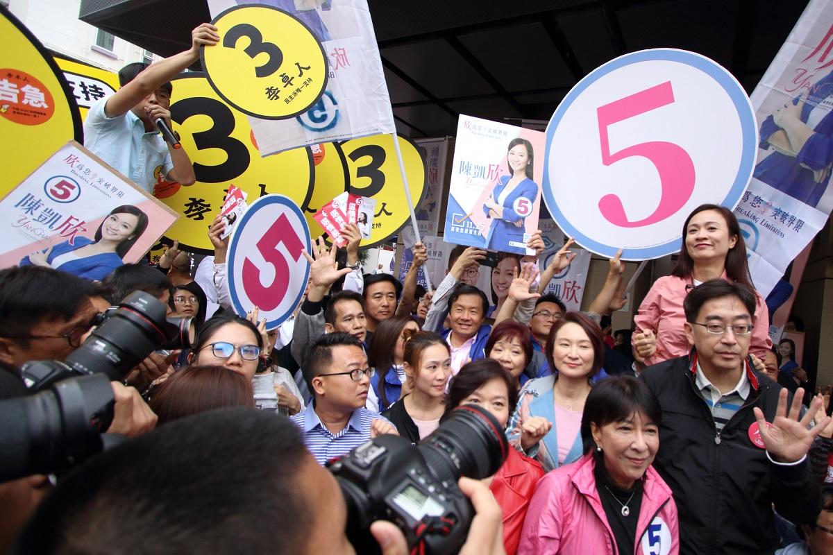香港眾志秘書長黃之鋒等人追擊正在拉票的陳凱欣團隊,質問為何多次拒絕出席選舉論壇。(蔡雯文/大紀元)