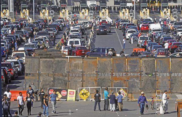 周日(11月25日),數百名大篷車成員企圖暴力闖美墨邊境,美方關閉聖伊西德羅(San Ysidro)入境口岸,並架設起巨大的金屬板。(Getty Images)