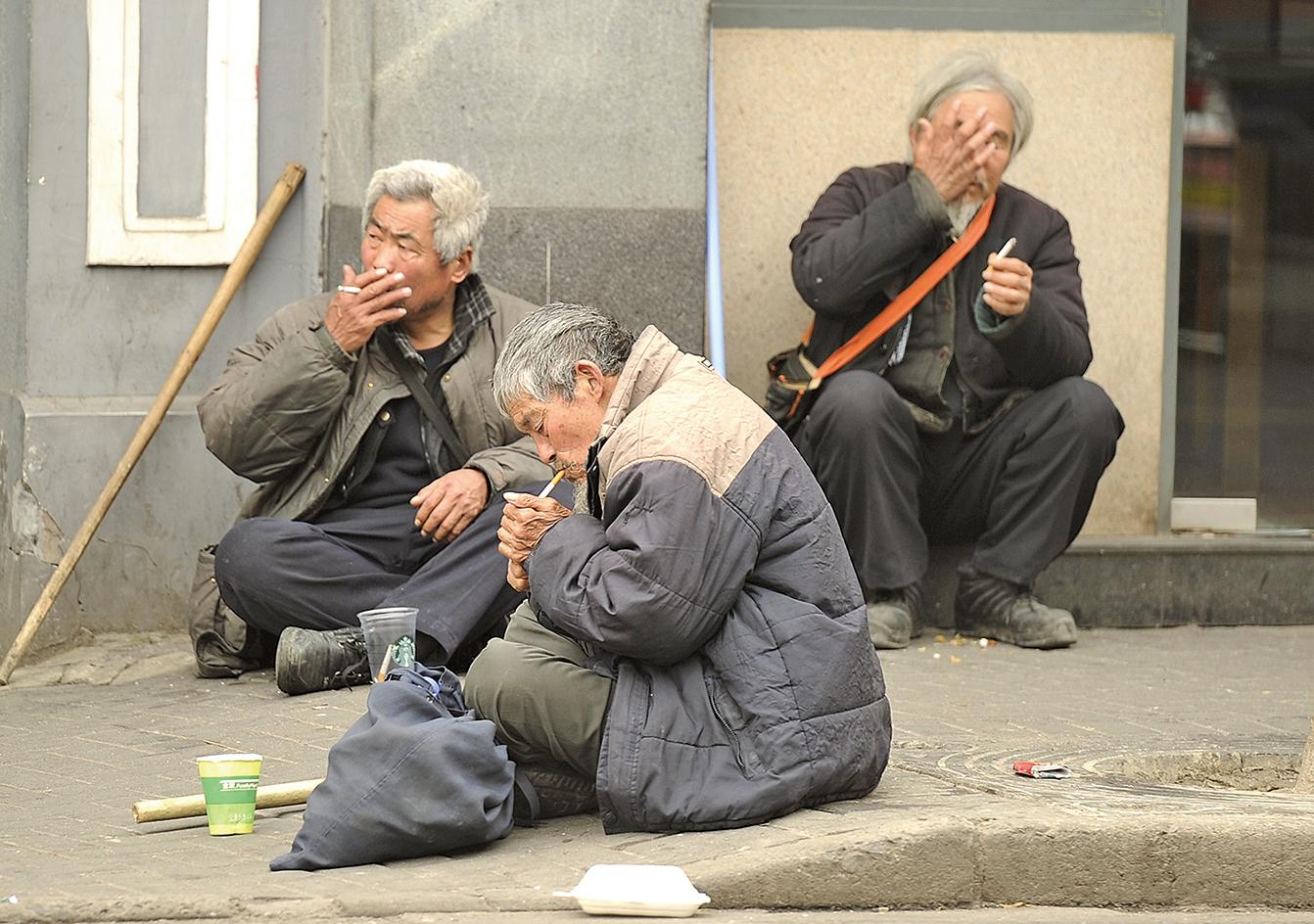 圖為在上海的一條街上,三位老年人正在吸煙。(AFP/GettyImages)