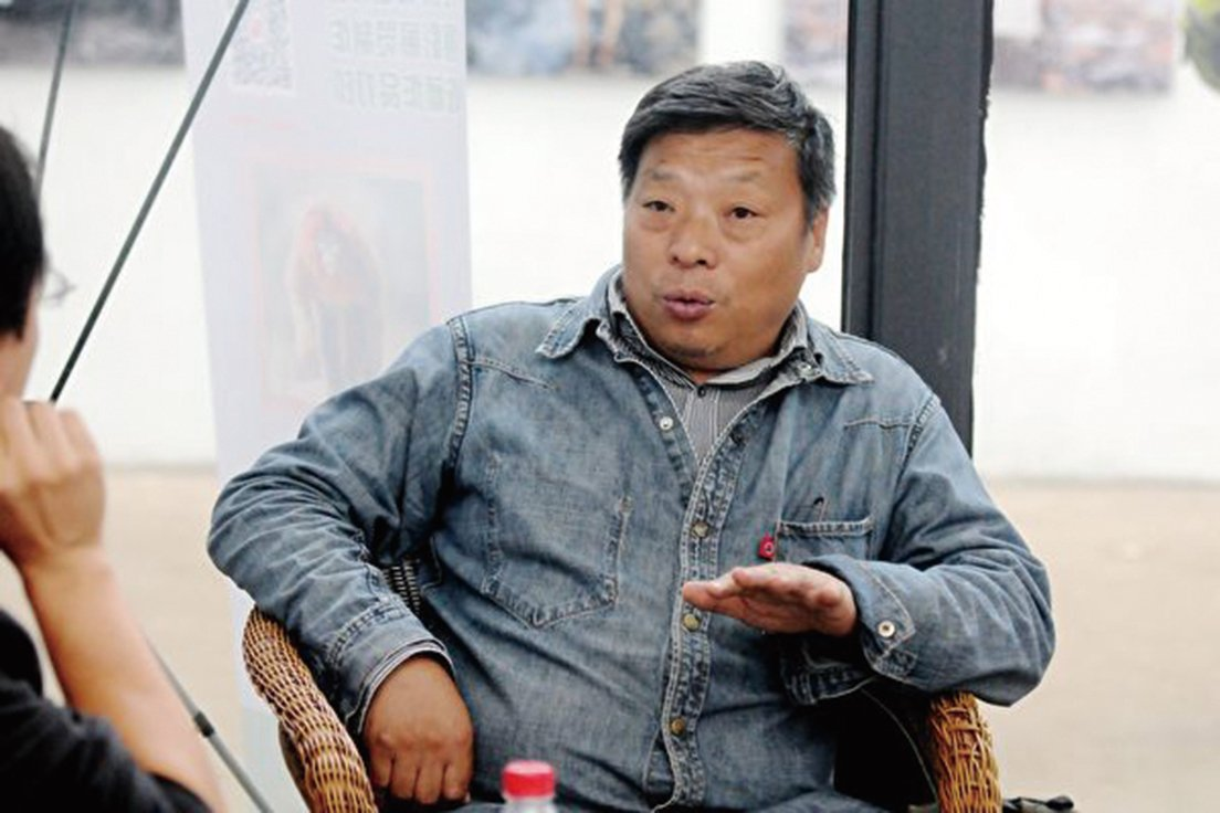 現居紐約持美國綠卡的中國紀實攝影師盧廣在新疆失聯,其妻子說,他是被國保帶走的。圖為盧廣在2014平遙國際攝影節上接受媒體採訪。(大紀元資料室)