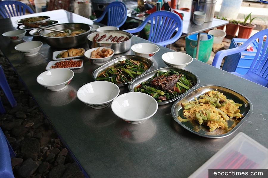 用「百家米」煮成的「有情有義百家飯」,以及用義工各自帶來的食物煮成的餸菜。(陳仲明/大紀元)