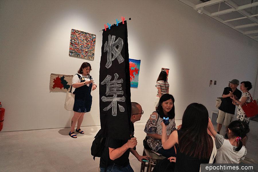 林東鵬舉著印有「收集」二字的紡布在CHAT六廠暑假期間的活動遊走,與市民互動,收集各種各樣有關「布」的故事。(曾蓮/大紀元)