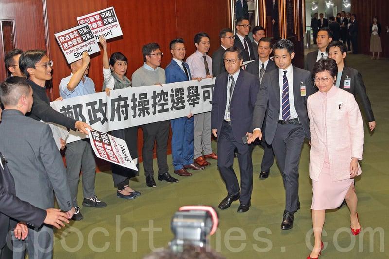林鄭月娥進入立法會出席答問大會時,一班民主派議員在會議廳門口列隊,手持抗議標語及喊口號。(李逸/大紀元)