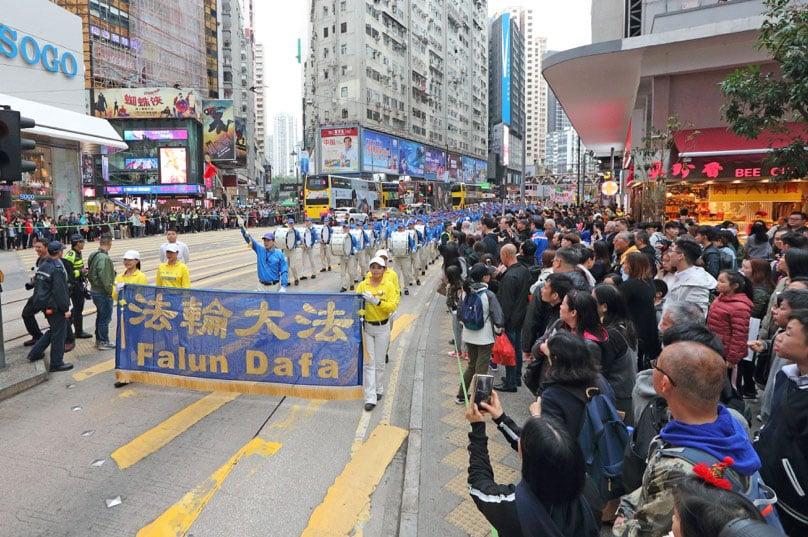 香港法輪功學員12月9日舉行國際人權日大遊行,呼籲制止中共對法輪功的迫害,圖為遊行隊伍途經銅鑼灣鬧市,天國樂團的奏樂吸引大批市民遊客觀看和拍攝。(李逸/大紀元)