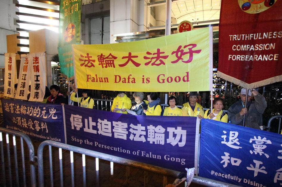 香港法輪功學員12月9日舉行國際人權日大遊行,呼籲制止中共對法輪功的迫害,法辦元兇。圖為法輪功學員在中聯辦門外讀信。(蔡雯文/大紀元)