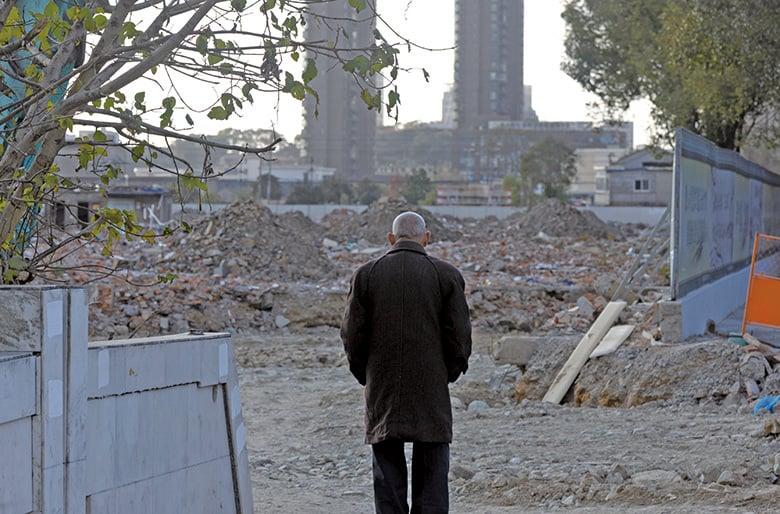 2014年12月25日,浙江省舟山市定海區,一位老人站在一處老住宅的廢墟前。(大紀元資料室)