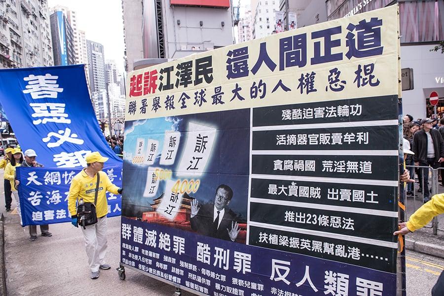 香港法輪功學員12月9日舉行國際人權日大遊行,呼籲制止中共對法輪功的迫害。圖為呼籲起訴江澤民群體滅絕罪、反人類罪的大型展板車。(余鋼/大紀元)
