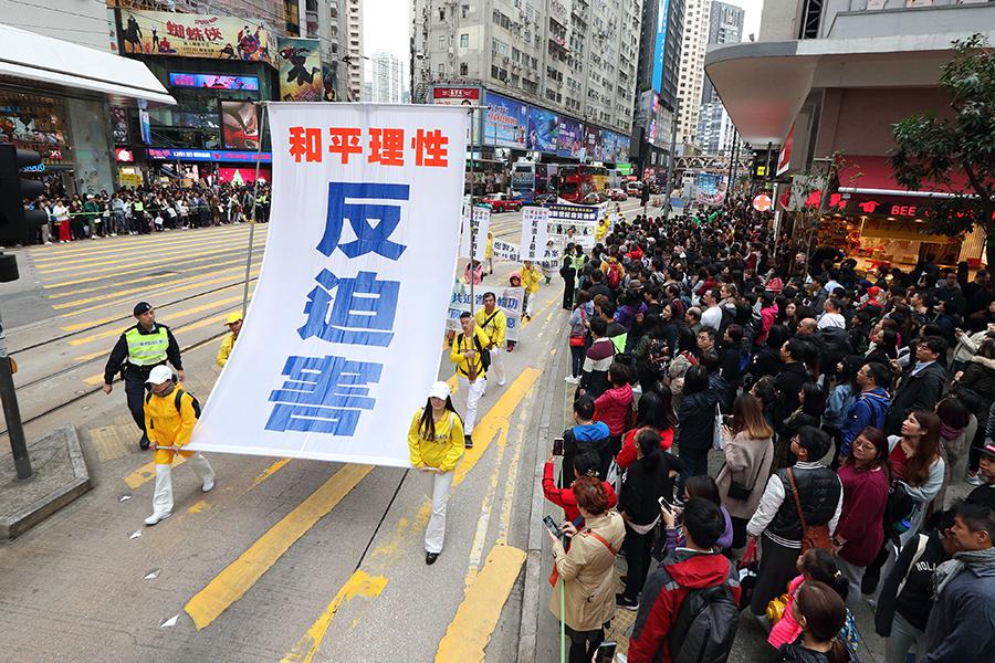 香港法輪功學員12月9日舉行國際人權日大遊行,呼籲制止中共對法輪功的迫害,圖為「和平理性反迫害」巨型橫幅。(李逸/大紀元)