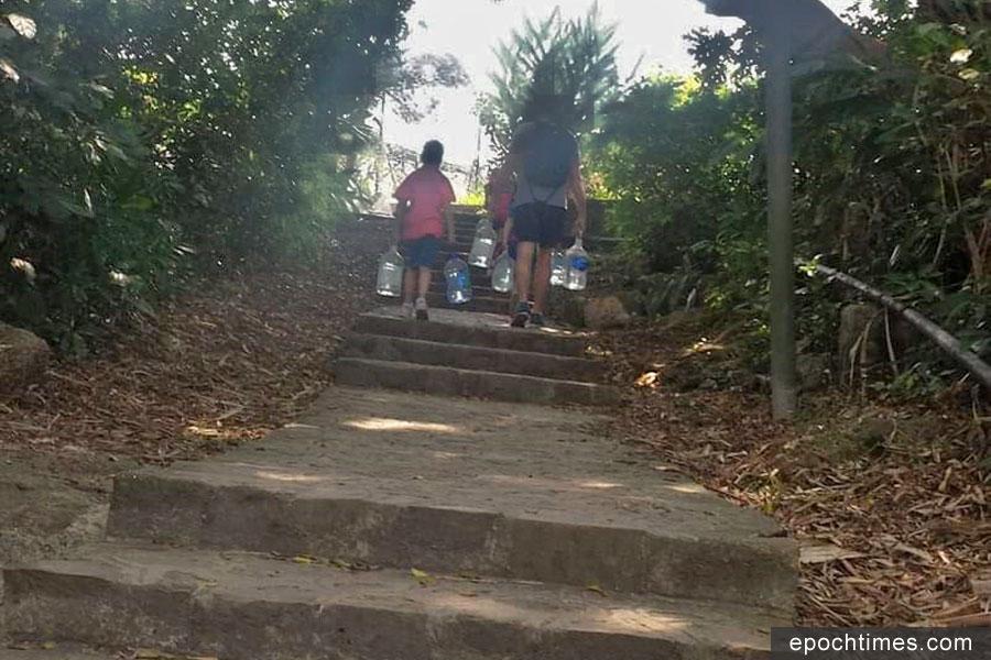 水塘無水時,坤記姊妹要去井邊打水運回店鋪,有遊客一家伸出援手,協助她們拿水上樓梯。(受訪者提供)
