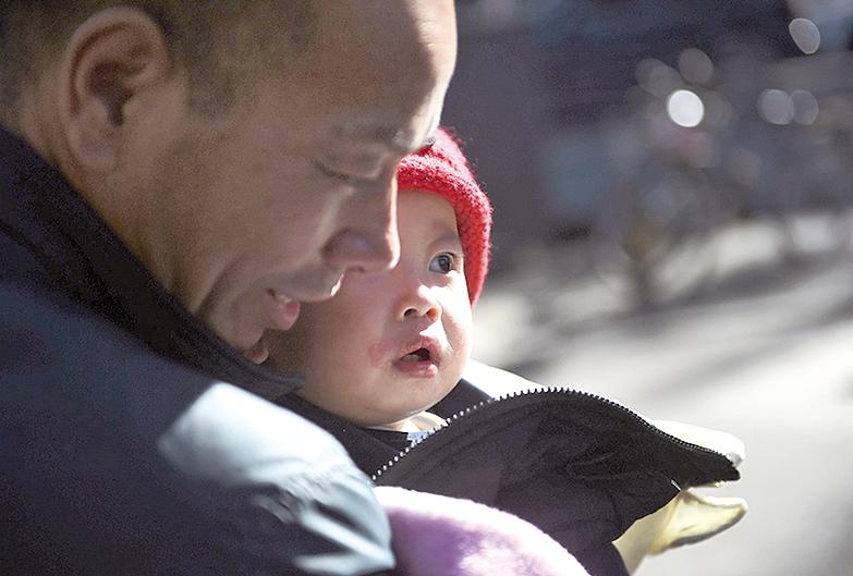 中共當局日前宣布,開放無戶口人員登記戶口。圖為北京一名老人抱著自己的孫子。(AFP)