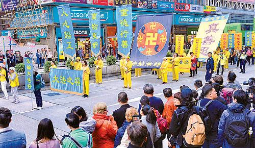 法輪功隊伍沿著彌敦道遊行,馬路兩旁的市民及遊客佇足觀看及拍照。(宋碧龍/大紀元)