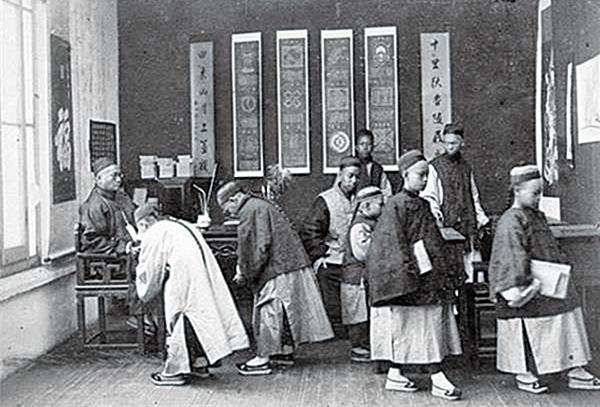 傳統文化的內涵是靠幾千年來的耳濡目染、身體力行、心口相傳而溶在了中國人的血脈中,從而達到智識相長,代代傳承。圖為老照片中的民國私塾。(公有領域)