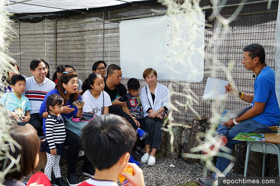 財哥在蝴蝶園中為家長和小朋友講解生態知識,眾人用心聆聽。(陳仲明/大紀元)