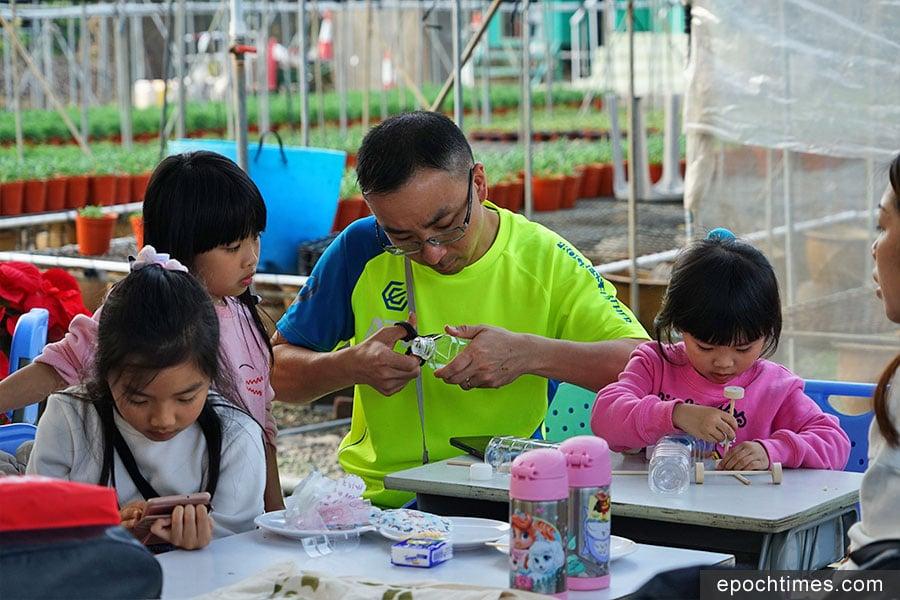 家長和小朋友正在用心以回收的膠樽製作含羞草環保車。(陳仲明/大紀元)