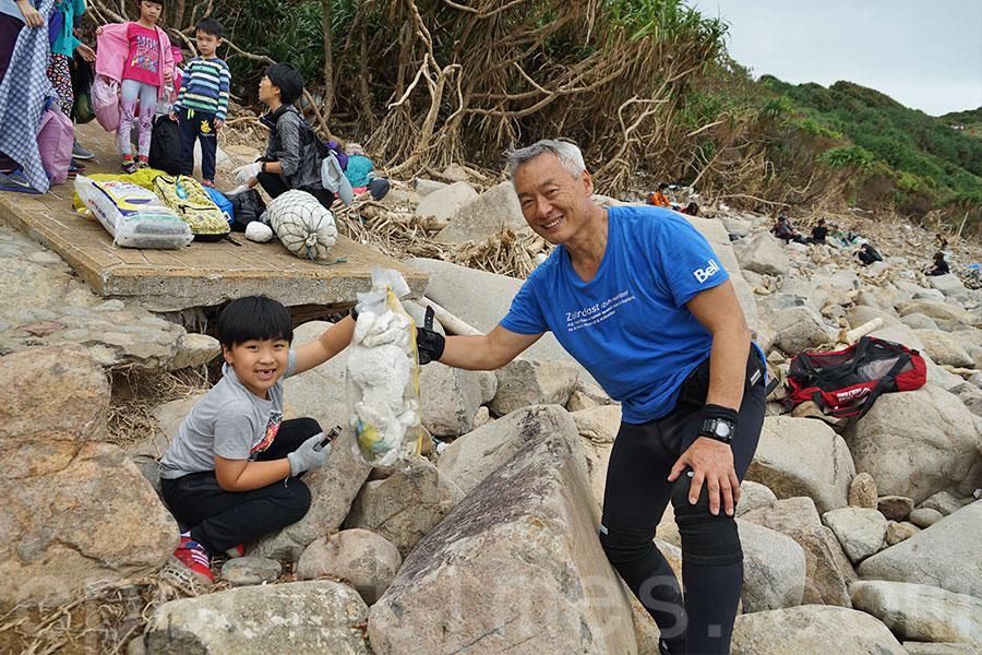 陳天明(右)一同參與了淨灘活動,他熱心為小朋友講解發泡膠、海洋垃圾對自然環境和人類帶來的危害。(曾蓮/大紀元)