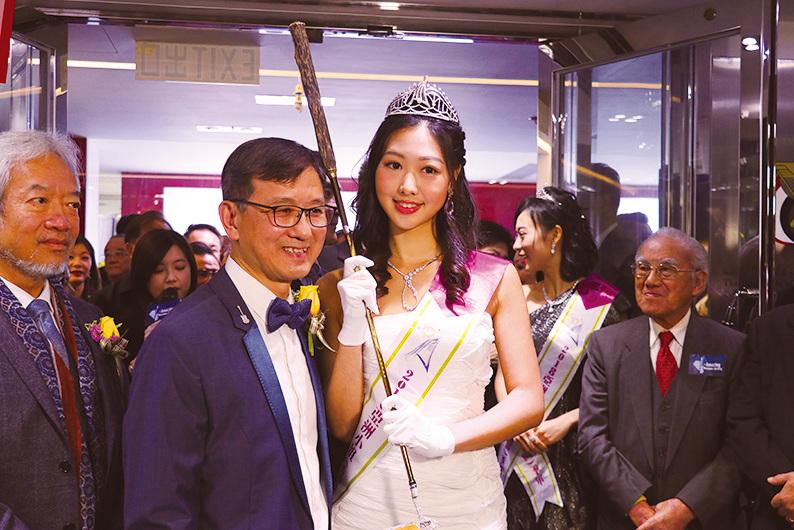 2018亞洲小姐冠軍梁雪瑤(右)手持高爾夫球桿,陪同沈運龍(左)接受健力士認證官頒獎。(陳仲明/大紀元)