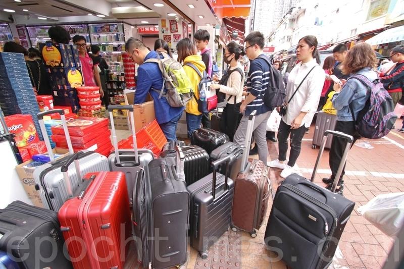 在上水的藥房外,大量大陸人聚集,他們的隨身行李箱阻礙行人道路。(蔡雯文/大紀元)