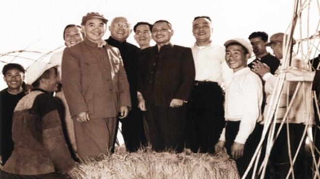 1958年10月18日,鄧小平由人托扶,站在稻子上與人合照留念。(資料圖片)