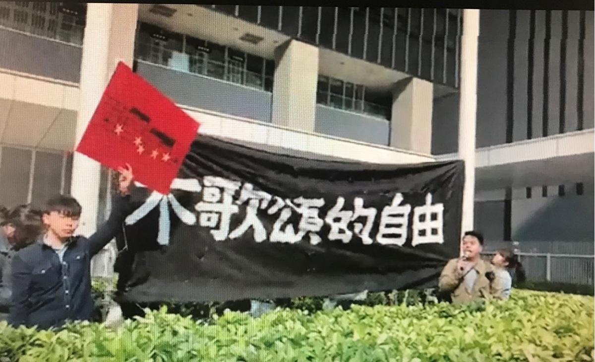 香港眾志多名成員將「不歌頌的自由」的標語,綁在公民廣場的五星紅旗旗杆上,抗議中共箝制市民表達權利。(香港眾志視頻截圖)