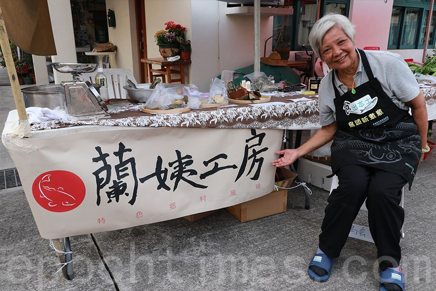 大生圍的村民蘭姨開設活動攤位,親手製作茶果、年糕,並提供本地出產的烏頭魚供遊人品嚐,推廣本地漁業。(陳仲明/大紀元)