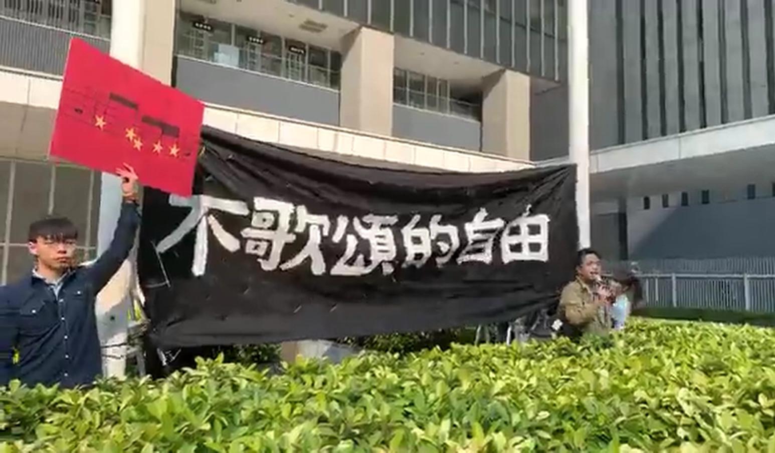 香港眾志多名成員昨晨進入公民廣場內的花槽內,將一幅寫上「不歌頌的自由」的橫額掛在旗桿上。(影片擷圖)