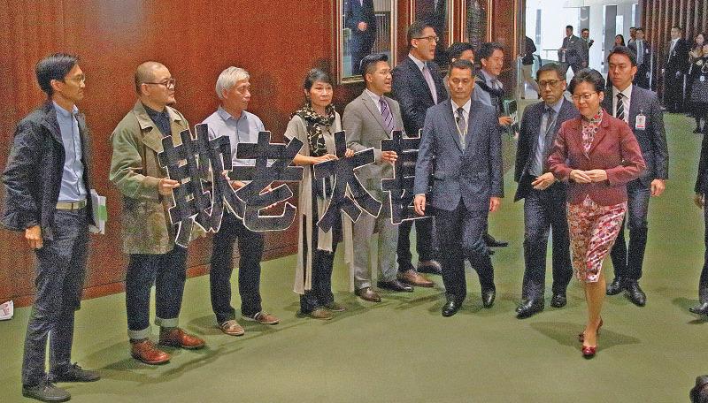 八名民主派議員在立法會議事廳外手持寫有「欺老太甚」的紙牌,抗議政府收緊長者綜援門檻,又在林鄭月娥經過時叫口號。(蔡雯文/大紀元)