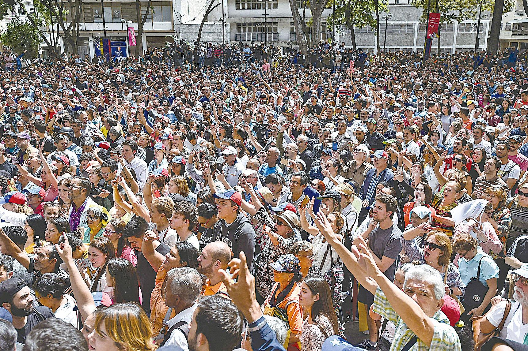 圖為2019年1月25日,委內瑞拉首都街頭集會抗議的民眾。 (Photo by Luis ROBAYO / AFP)