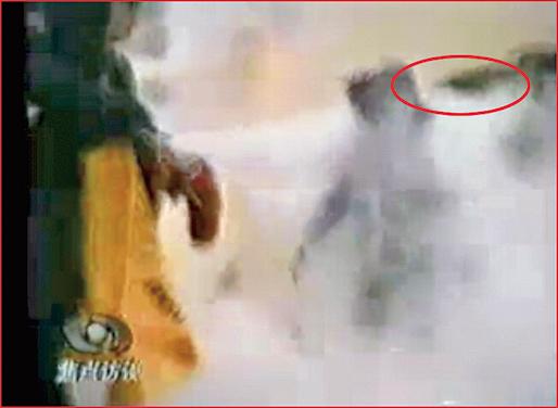 CCTV「自焚」節目慢動作分析 在滅火器噴射的同時,一隻手臂掄了起來,猛擊劉春玲的頭部。
