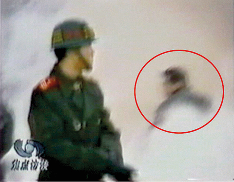 CCTV「自焚」節目 慢動作分析 一名穿大衣的男子正好站在出手打擊的方位,仍然保持著一秒鐘前用力打擊的姿勢。