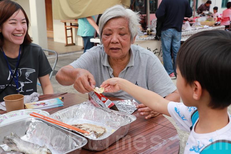 蘭姨請參與活動的小朋友試吃自家養殖的「生態魚」。(陳仲明/大紀元)