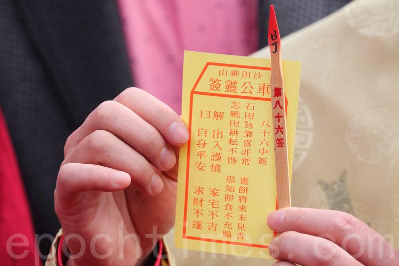 劉業強為香港求得八十六籤「中籤」,車公廟外的解籤師傅陳天恩指,此籤是中下籤,籤頭為「話梅止渴」,即是「得個睇字」,寓意非常差。(李逸/大紀元)
