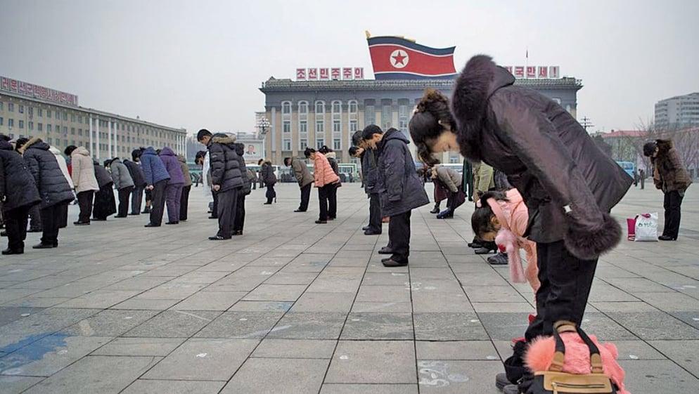 圖為朝鮮人在平壤金日成廣場上向金正日父子的畫像鞠躬的場面。(AFP)