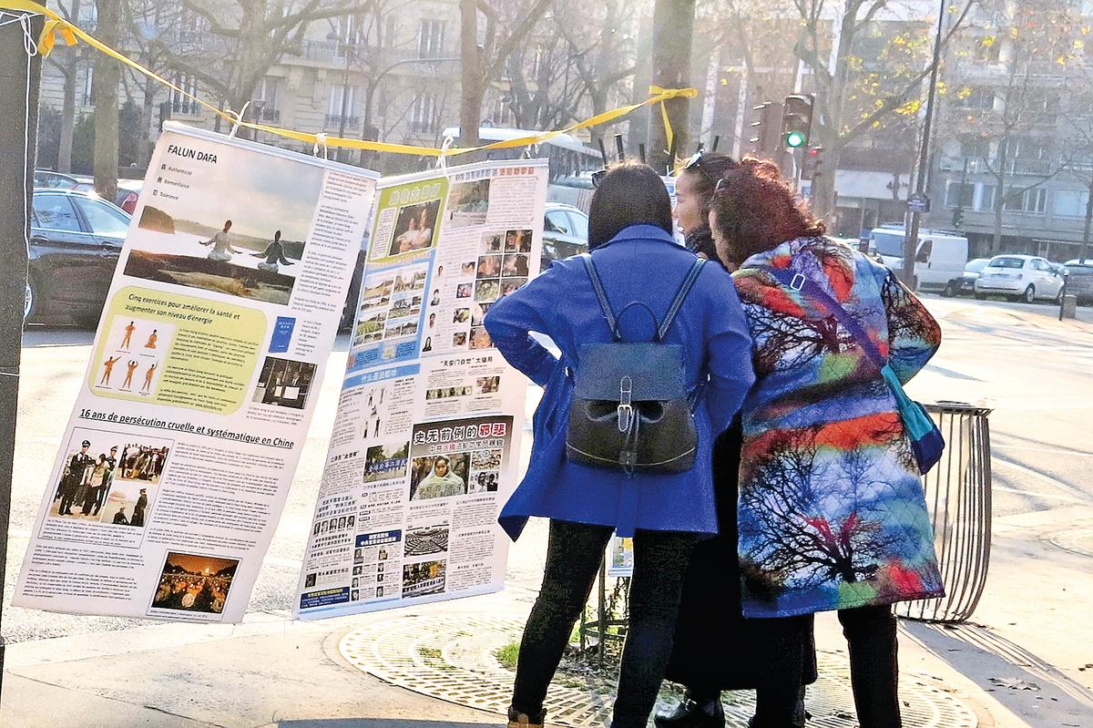中國大陸遊客在巴黎埃菲爾鐵塔附近的法輪功真相點駐足閱讀真相展板。 (明慧網)