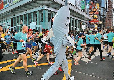 趣怪裝扮也是渣馬特色,打扮成鯊魚的跑手落力奔跑。(陳仲明/大紀元)
