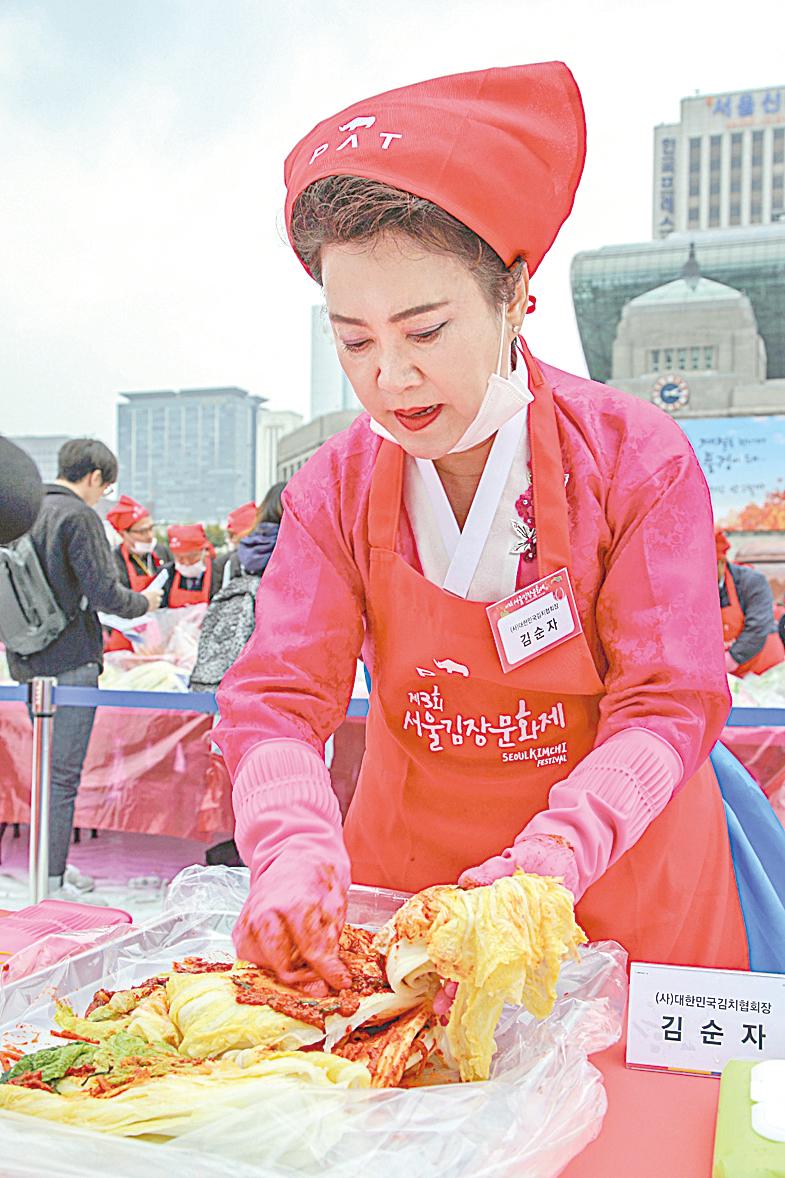 南韓泡菜慶典中,正在製作泡菜的婦人。
