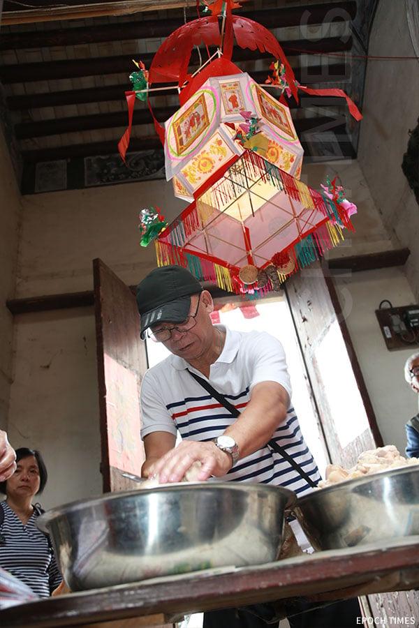 山貝村村民在祠堂內分丁肉。(陳仲明/大紀元)
