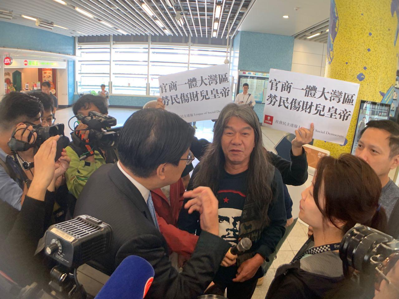 社民連成員包圍到場出席宣講會的港鐵董事局非執行主席馬時亨。(李逸/大紀元)