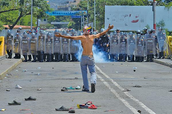 上周六(2月23日),委內瑞拉總統馬杜羅的軍隊及裝甲車,在委國與哥倫比亞及巴西的邊境,以催淚彈及橡膠子彈攻擊保護人道物資進入委國的平民,造成至少兩人死亡。(LUIS ROBAYO/AFP/Getty Images)
