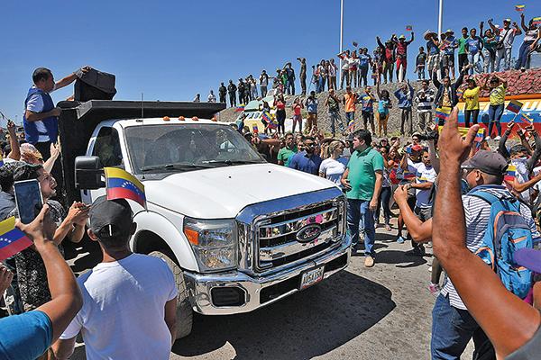 由委國人駕駛並由巴西警察護送的貨車,由巴西進入委國邊境。圖為人們歡呼首批救援物資進入委國。但貨車遭委國國民警衛軍阻擋進入。(NELSON ALMEIDA/AFP/Getty Images)