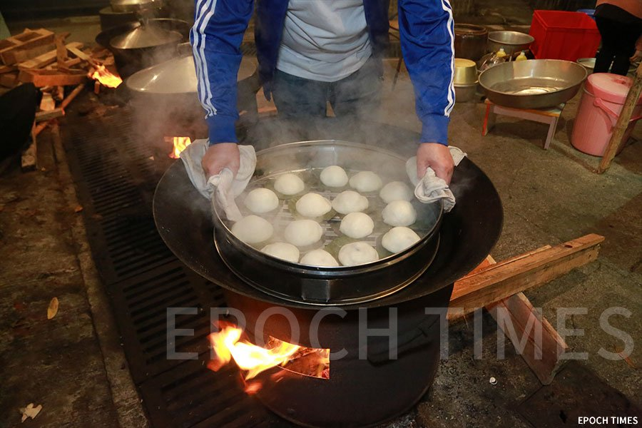 村民以柴火蒸煮蘿蔔茶果。(陳仲明/大紀元)