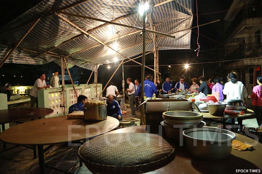村民在戲棚一旁架設煮食棚,以柴火烹煮傳統食品。(陳仲明/大紀元)