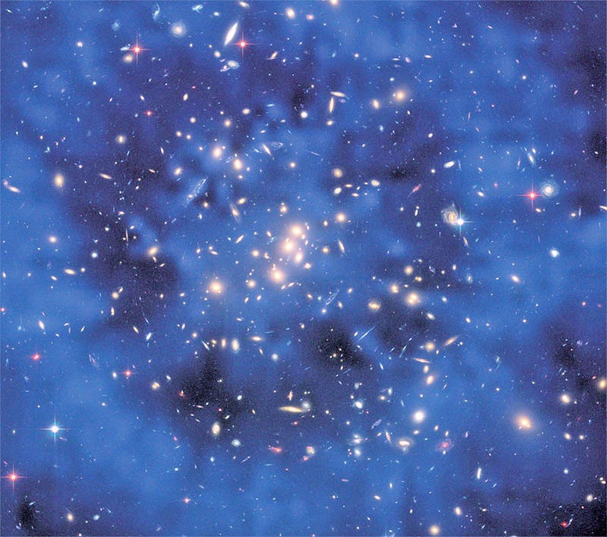 從引力透鏡產生的效應,星系團CL0024+17內部被發現存在有一個暗物質圈,在這張哈伯太空望遠鏡相片裏以藍色顯示出來。(NASA)
