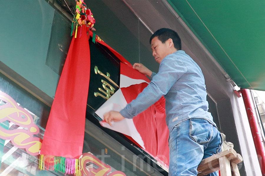 掛牌儀式在早上11時舉行,在正門的紅紙揭開,露出新招牌。(陳仲明/大紀元)